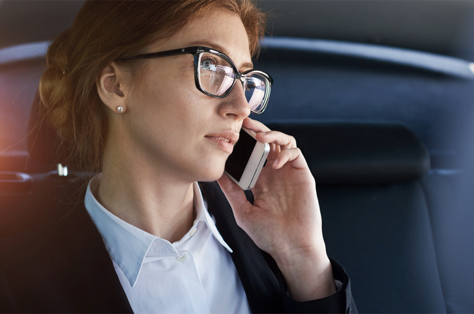 red haired woman with glasses on mobile phone
